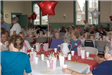 Senior citizens sit at tables together decorated with star balloons and popcorn buckets.