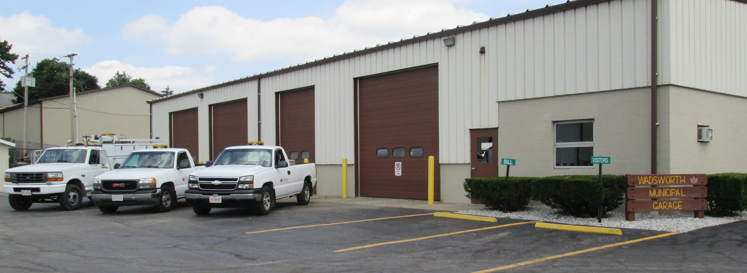A large garage building with white trucks parked in front.