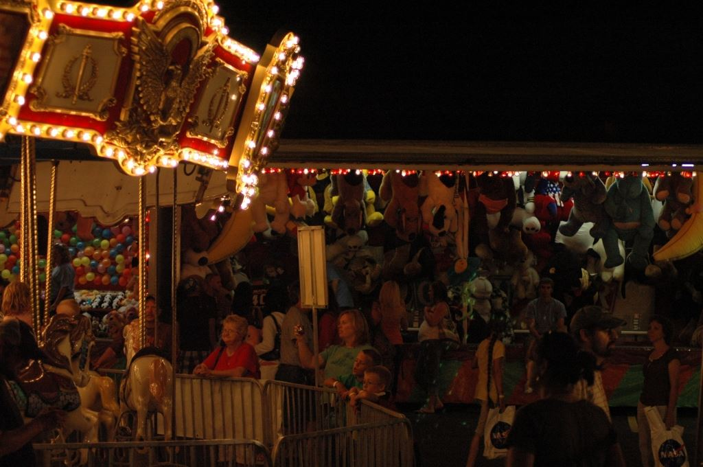 Crowd in Front of Carousel and Other Games at Carnival