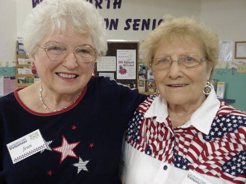 Two women volunteers smile together.