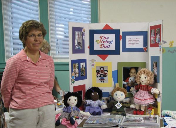 Woman stands next to her The Giving Doll table display.